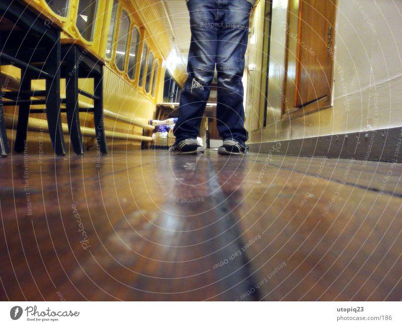 Froschperspektive 2 Schuhe Schiffsplanken Reflexion & Spiegelung Wasserfahrzeug Mann Beine Jeanshose Flur Stuhl x-beinig Gang