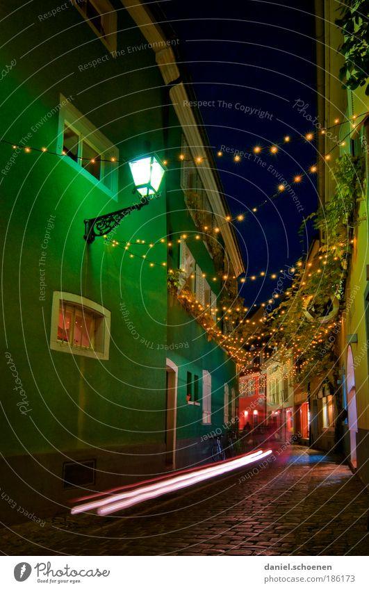und immer fährt einem ein Radfahrer durchs Bild blau grün Wege & Pfade Bewegung Lampe Weihnachten & Advent Verkehr Verkehrswege Kopfsteinpflaster fahren Gasse Altstadt Lichterkette Freiburg im Breisgau Weihnachtsbeleuchtung