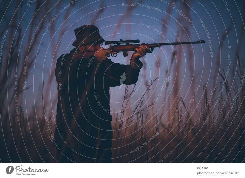 Jäger, der Opfer auf Feld mit seinem Gewehr im Sonnenaufgang zielt Natur Mann Erwachsene Senior Lifestyle Sport Gras wild Freizeit & Hobby 45-60 Jahre