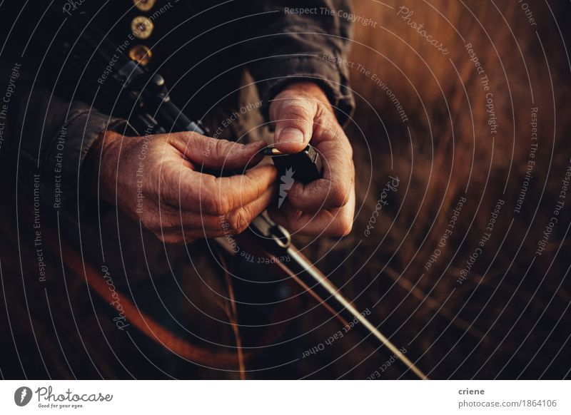 Schließen Sie oben vom Jäger, der seine Schrotflinte mit Kugeln lädt Freizeit & Hobby Jagd Sport Mann Erwachsene Männlicher Senior Hand Umwelt Natur Wärme Feld