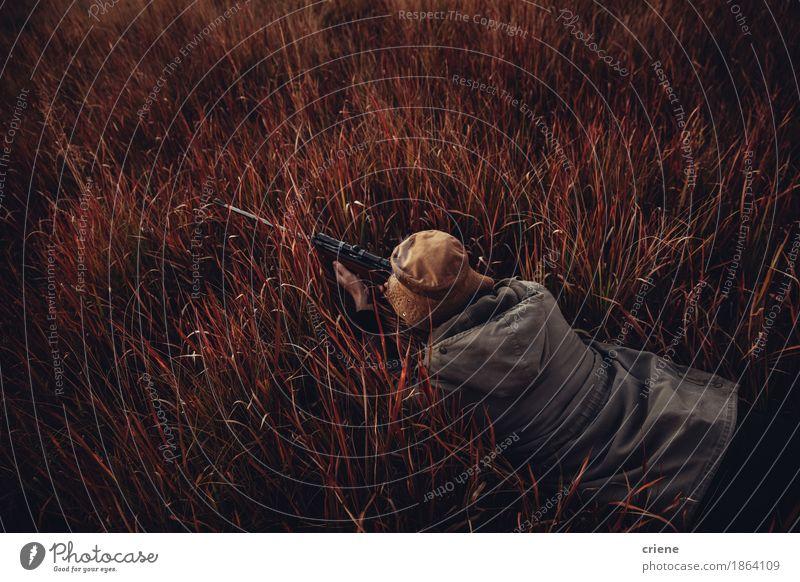 Hohe Winkelsicht von Hunter legend in hohes rotes Gras Lifestyle Freizeit & Hobby Jagd Sport Mann Erwachsene Natur Landschaft genießen liegen wild Leidenschaft