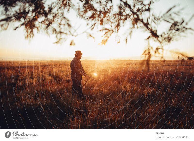 Jäger zielt auf ein Feld mit seinem Gewehr und Patrone im Sonnenaufgang Mensch Mann Landschaft Tier Erwachsene Senior Lifestyle Sport Gras Spielen maskulin