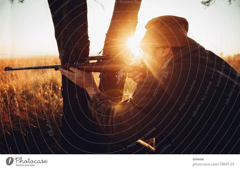 Jäger, der hinter Baum auf dem Feldschießen des wilden Tieres sich versteckt Fleisch Lifestyle Freizeit & Hobby Jagd Sport Erfolg maskulin Mann Erwachsene