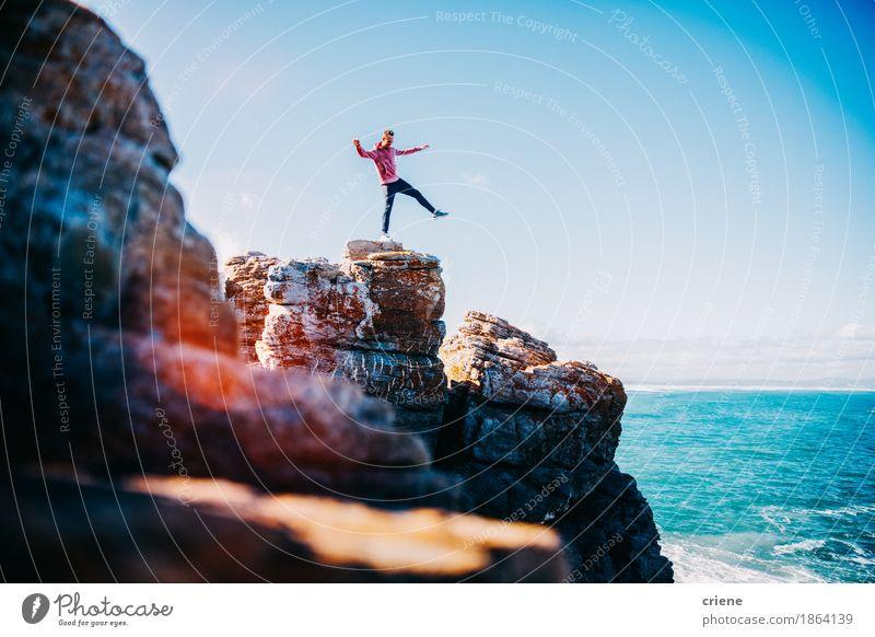 Junger Mann, der auf Klippe durch den Ozean balanciert Ferien & Urlaub & Reisen Jugendliche Sommer Meer Freude Strand Berge u. Gebirge Leben Lifestyle klein