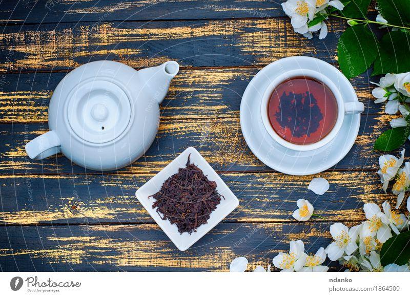 Schwarzer Tee in einer weißen Tasse und Untertasse und Jasminblüten Kräuter & Gewürze Frühstück Tisch Pflanze Blume Blatt Holz frisch heiß braun gelb grün