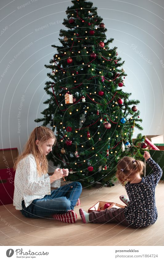Junges Mädchen und ihre kleine Schwester, die Weihnachtsbaum verziert Lifestyle Freude Dekoration & Verzierung Feste & Feiern Weihnachten & Advent Kind