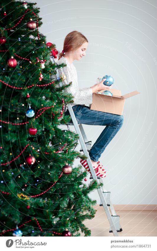 Junges Mädchen, das zu Hause Weihnachtsbaum mit Bällen verziert Lifestyle Freude Dekoration & Verzierung Feste & Feiern Weihnachten & Advent Mensch Kind 1