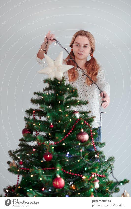 Junges Mädchen, das zu Hause Weihnachtsbaum mit Lichtern verziert Lifestyle Freude Dekoration & Verzierung Feste & Feiern Weihnachten & Advent Mensch Kind 1