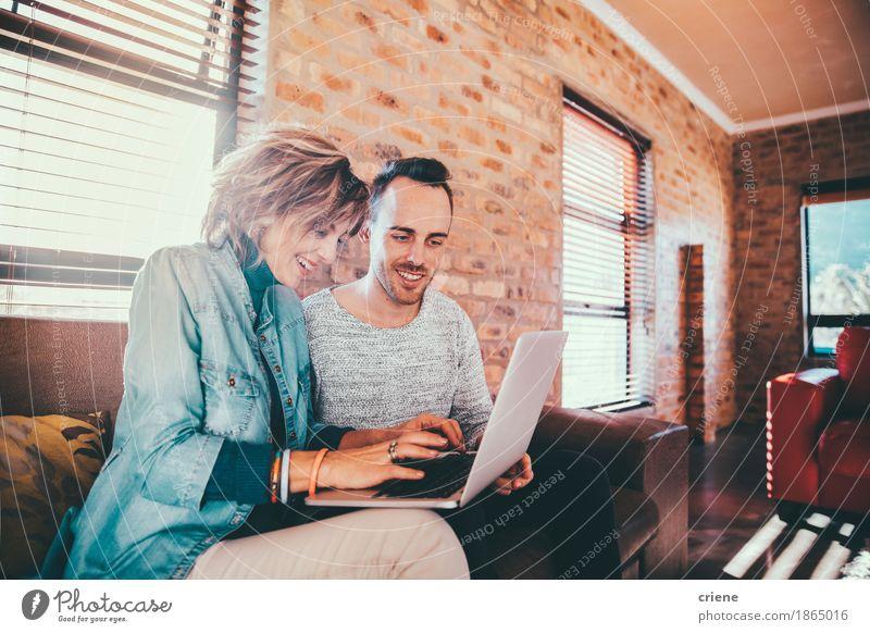 Mutter und Sohn, die zusammen auf Laptop grasen Haus Freude Erwachsene Lifestyle Familie & Verwandtschaft lachen Business Zusammensein Büro modern