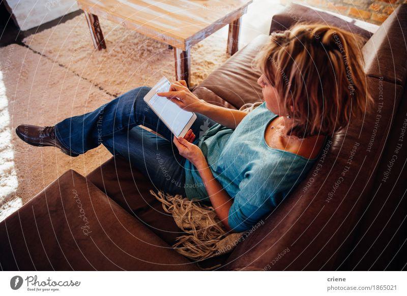 reife Frau, die auf Sofa unter Verwendung der digitalen Tablette sitzt Lifestyle lesen Haus Wohnzimmer Büro Business Computer Technik & Technologie