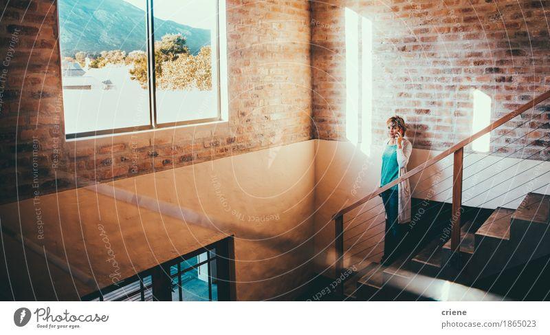Reife Frau, die auf Smartphone bei der Stellung auf Treppe spricht Lifestyle Freude Häusliches Leben Haus Traumhaus Innenarchitektur Arbeit & Erwerbstätigkeit