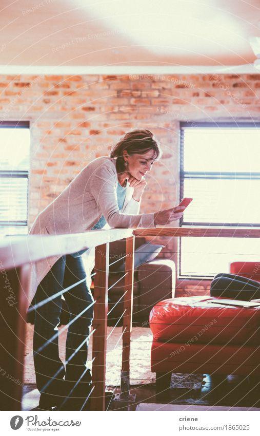 Reife Frau liest Nachricht auf ihrem Smartphone lesen Wohnzimmer Arbeit & Erwerbstätigkeit Arbeitsplatz Büro Business Mittelstand Telefon Handy PDA