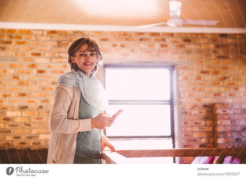 Reife Frau, die an der Kamera beim Halten von Smartphone lächelt Lifestyle Freude Häusliches Leben Wohnung Wohnzimmer Arbeitsplatz Büro Business Mittelstand