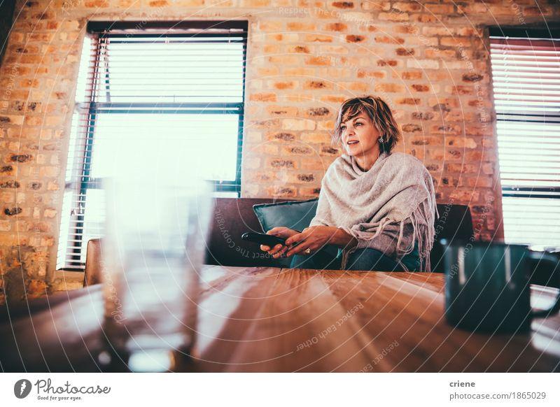 Reife Frau, die zu Hause fern sitzt auf Couch sitzt Freude Erwachsene Senior Lifestyle Glück Wohnung Freizeit & Hobby Häusliches Leben modern