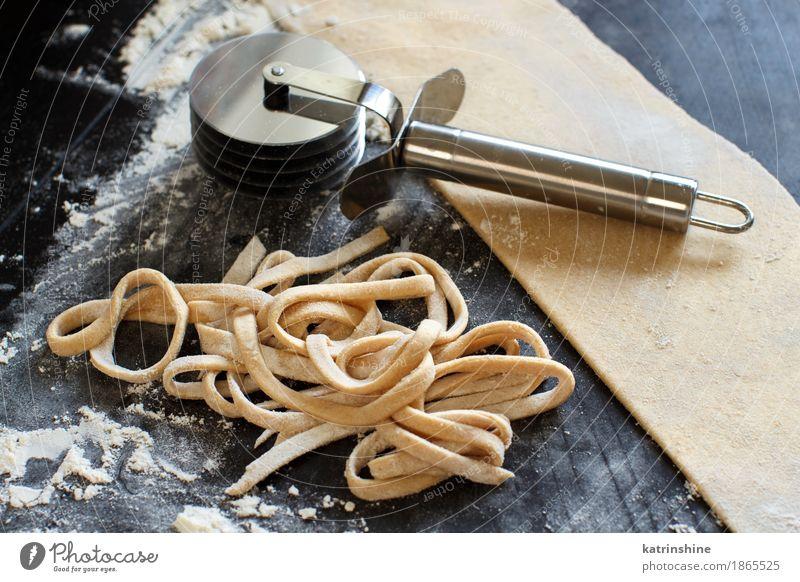 Making hausgemachte Taglatelle mit einer Pasta Rollschneider Teigwaren Backwaren Ernährung Diät Italienische Küche Tisch machen dunkel frisch Tradition Zutaten