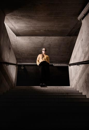 Herabschauend. feminin Junge Frau Jugendliche 1 Mensch 18-30 Jahre Erwachsene Architektur Mode Pullover Brille blond Zopf stehen warten Coolness dunkel einfach