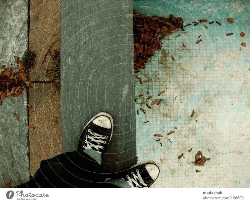 Jahreszeitenchaos Mann Erwachsene Einsamkeit Chucks Muster Boden Asphalt Bodenbelag Blatt Herbst stehen Jeansstoff Ecke Linie trashig Farbfoto Gedeckte Farben