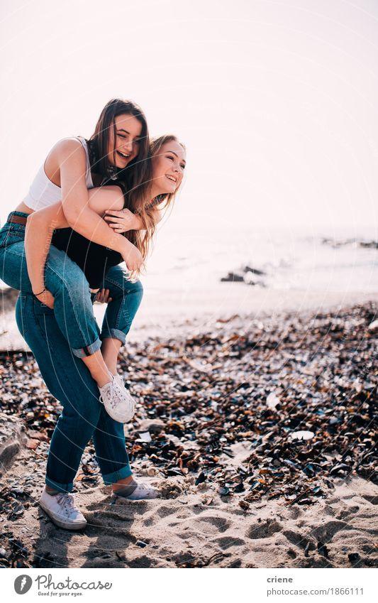 Glückliche kaukasische Jugendlichen, die Doppelpol auf dem Strand tun Mensch Sommer Junge Frau Meer Freude Mädchen Lifestyle Küste lachen Paar Tourismus