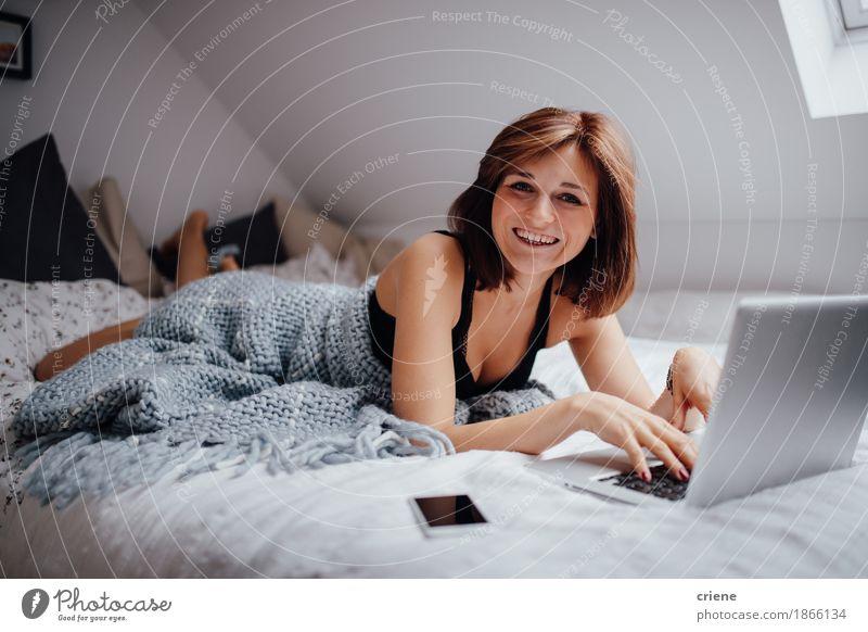 Junge kaukasische Frauen, die im Bett mit dem Laptoplächeln liegen Mensch Jugendliche schön Junge Frau Freude 18-30 Jahre Erwachsene sprechen Lifestyle feminin