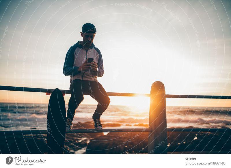 Hippie-Kerl, der auf dem Geländerbrowsen mit seinem intelligenten Telefon sitzt Lifestyle Freizeit & Hobby Sommer Handy PDA Technik & Technologie