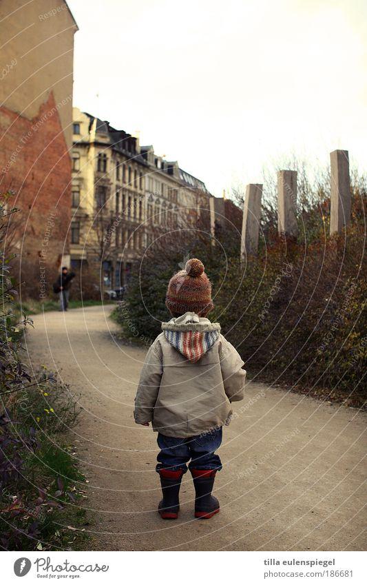 klein Spielen maskulin Kleinkind Kindheit 1 Mensch Herbst schlechtes Wetter Haus Jacke Gummistiefel Mütze beobachten entdecken Blick stehen warten Erwartung