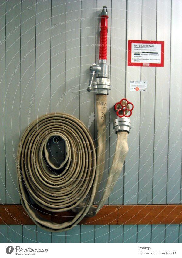 Im Brandfall Feuerlöscher Schlauch Hebel hängen rot Wand brennen Notfall Unfall Industrie Angst Panik Hilfsbereitschaft aufgerollt Feuerwehr Wasserhahn