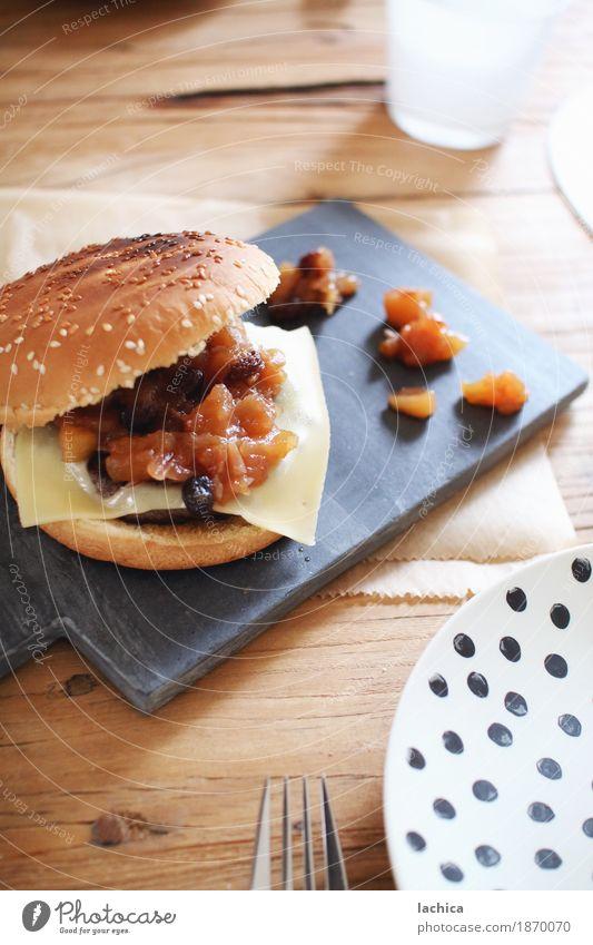 Burger mit Chutney Fleisch Käse Frucht Apfel Brot Rosinen Essen Mittagessen Picknick Hamburger Cheeseburger Teller Gabel Tisch Schneidebrett Holz füttern