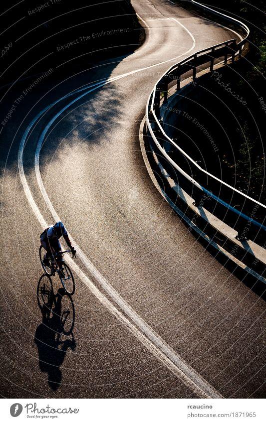 Radfahrer, der entlang eine gepflasterte Gebirgsstraße fährt Erholung Sommer Sport Mann Erwachsene Straße Fitness Einsamkeit Gegenlicht Fahrrad Radfahren