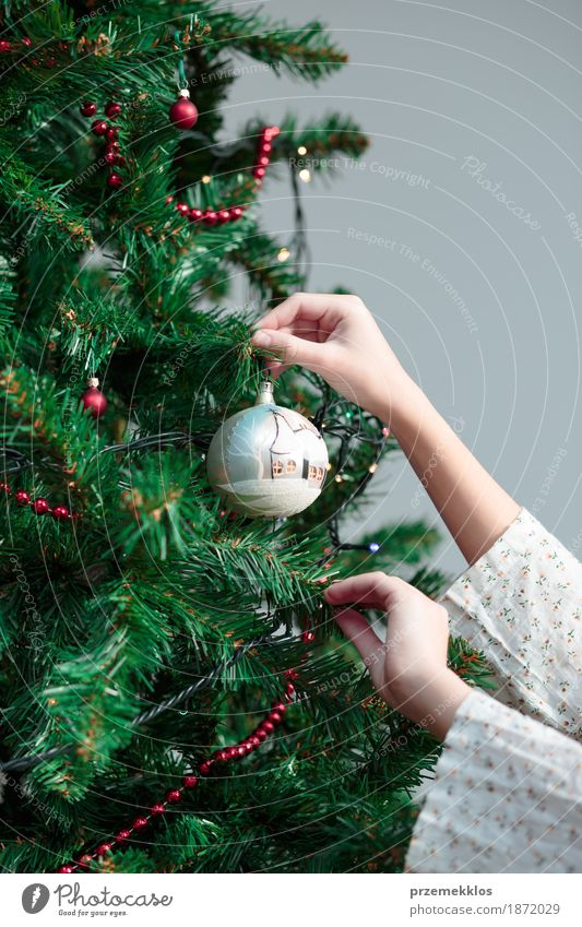 Junges Mädchen, das zu Hause Weihnachtsbaum mit Ball verziert Lifestyle Freude Dekoration & Verzierung Feste & Feiern Weihnachten & Advent Mensch Arme Hand 1