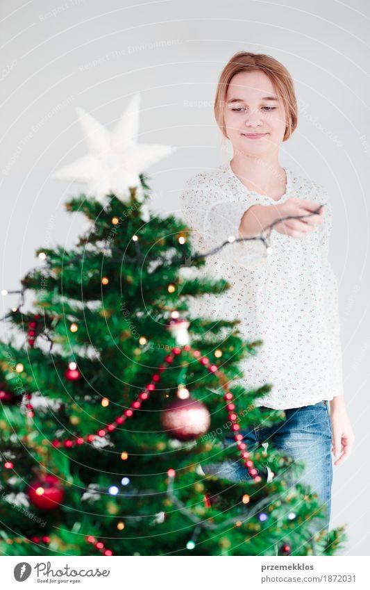 Junges Mädchen, das zu Hause Weihnachtsbaum mit Lichtern verziert Lifestyle Freude Dekoration & Verzierung Feste & Feiern Weihnachten & Advent Mensch