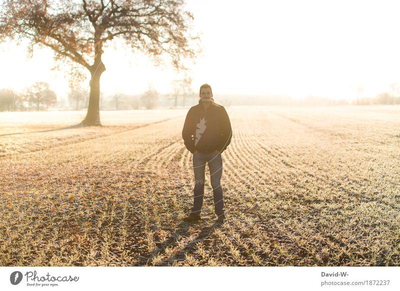 Mann steht bei Frost draußen auf dem Acker Kälte Sonnenlicht Sonnenstrahlen Sonnenuntergang Licht gelb Ackerboden gefroren hände in den taschen