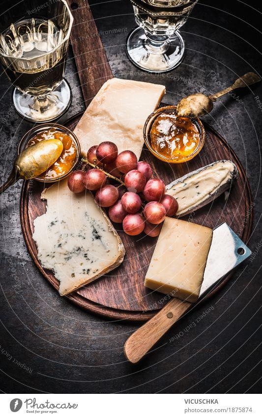 Feine Käseauswahl mit Wein, Honig-Senf-Sauce und Trauben Stil Lebensmittel Party Design Frucht Ernährung Glas Tisch Getränk Restaurant Geschirr Dessert Messer