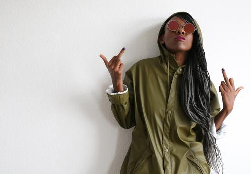 . feminin Frau Erwachsene 1 Mensch Mantel Sonnenbrille Haare & Frisuren schwarzhaarig langhaarig Rastalocken Afro-Look beobachten Blick Coolness rebellisch