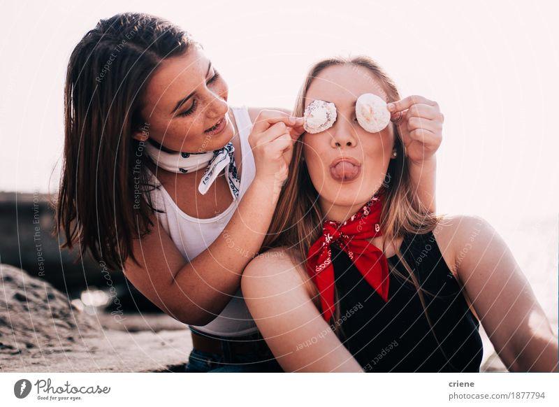 Jugendlich Mädchen, die Gesichter ziehen und mit Shell am Strand spielen Ferien & Urlaub & Reisen Jugendliche Junge Frau Freude Lifestyle lachen Tourismus