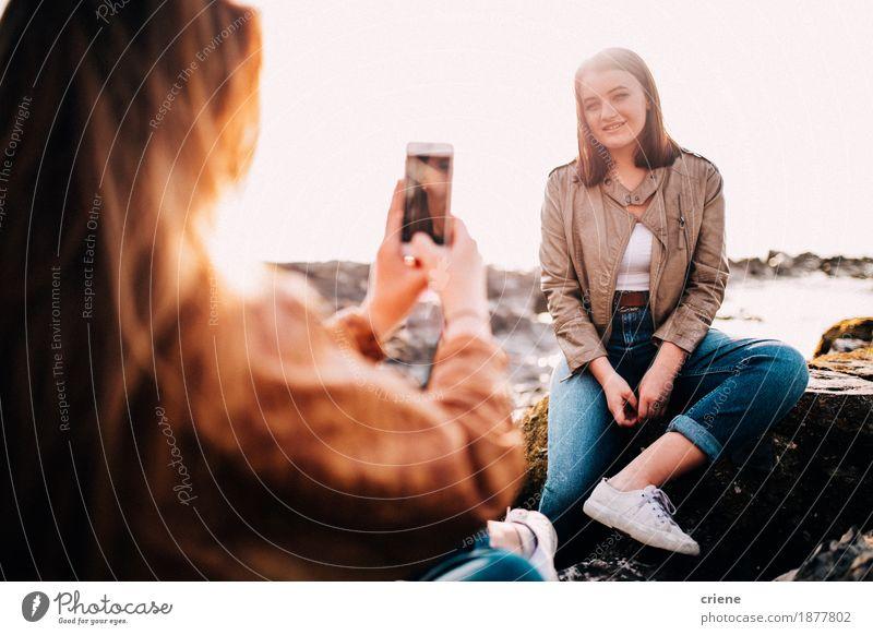 Mädchen, das Foto ihres Freunds mit Smartphone macht Lifestyle Freude Ferien & Urlaub & Reisen Strand Telefon Handy Fotokamera Technik & Technologie Internet