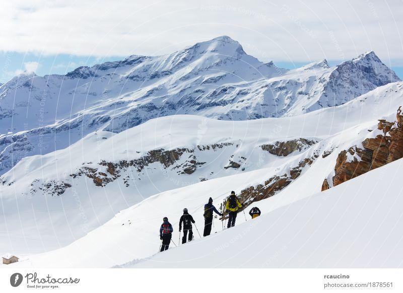 Eine Gruppe Freerider über einer schneebedeckten Berglandschaft. Ferien & Urlaub & Reisen Winter Schnee Berge u. Gebirge Sport Skifahren Junge Mann Erwachsene