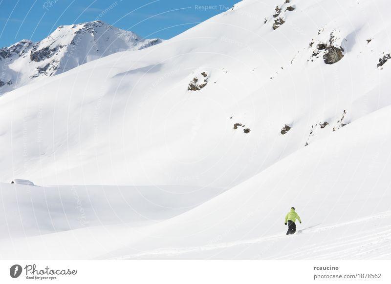 Snowboarder geht bergab über eine verschneite Berglandschaft. Ferien & Urlaub & Reisen Winter Schnee Berge u. Gebirge Sport Junge Himmel Alpen frieren