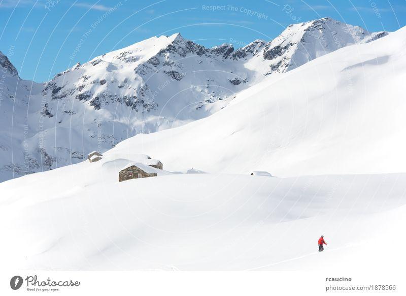 Snowboarder geht bergab über eine verschneite Berglandschaft Ferien & Urlaub & Reisen Winter Schnee Berge u. Gebirge Sport Junge Himmel Alpen frieren