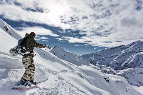 Snowboarder geht bergab über eine verschneite Berglandschaft. Himmel Natur Ferien & Urlaub & Reisen Mann weiß Landschaft Einsamkeit Winter Berge u. Gebirge