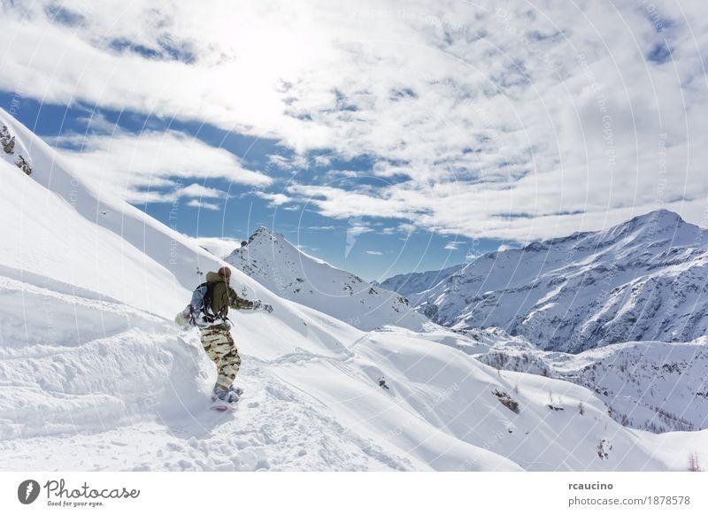 Snowboarder geht bergab über eine verschneite Berglandschaft Ferien & Urlaub & Reisen Tourismus Winter Schnee Berge u. Gebirge Sport Skifahren Skipiste Junge 1