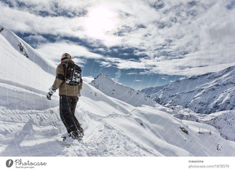 Snowboarder geht bergab über eine verschneite Berglandschaft. Ferien & Urlaub & Reisen Winter Schnee Berge u. Gebirge Sport Skifahren Junge Landschaft Himmel