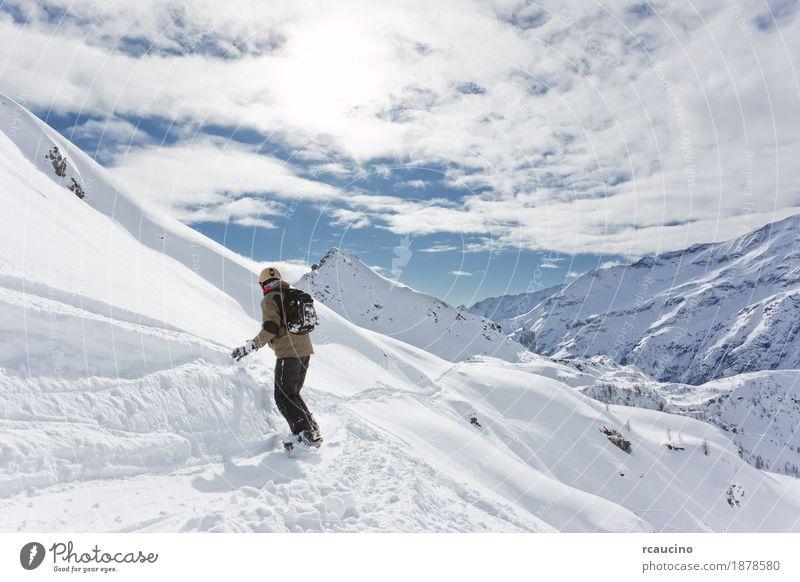 Snowboarder geht bergab über eine verschneite Berglandschaft Ferien & Urlaub & Reisen Winter Schnee Berge u. Gebirge Sport Skifahren Junge Landschaft Himmel