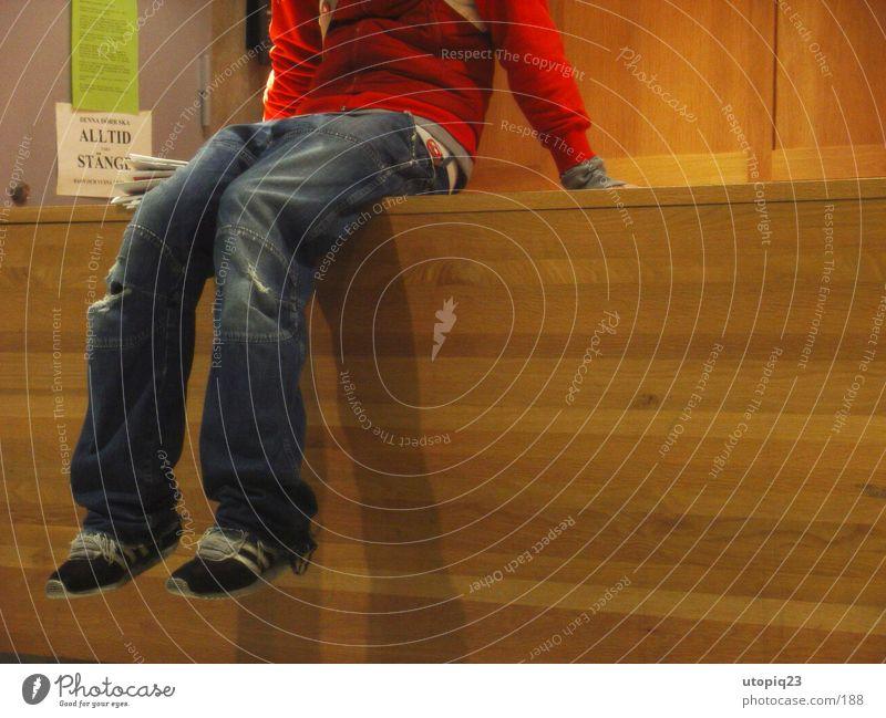 Warten Mann Holz Schuhe Beine warten sitzen Jeanshose Langeweile Theke Rezeption Holzmehl