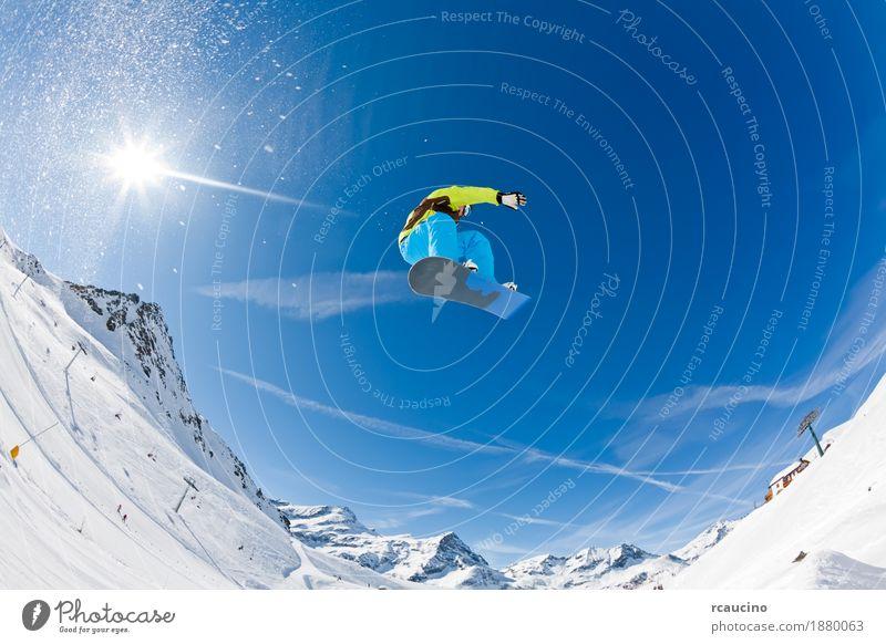 Snowboarder, der weg von einem Sprung startet Freude Ferien & Urlaub & Reisen Sonne Winter Schnee Berge u. Gebirge Sport Junge Mann Erwachsene Alpen springen
