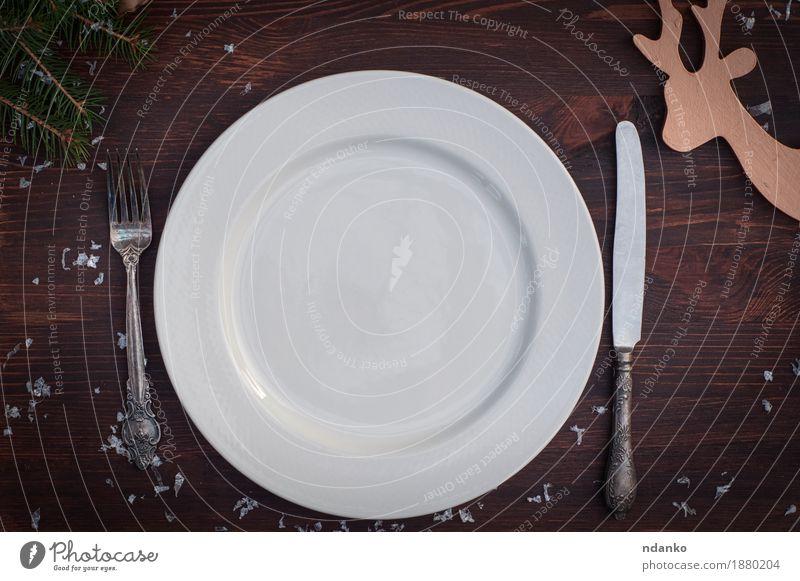 Weiße Platte mit silbernem Messer und Gabel auf brauner Holzoberfläche Frühstück Abendessen Festessen Geschirr Teller Winter Schnee Tisch Küche Restaurant Platz