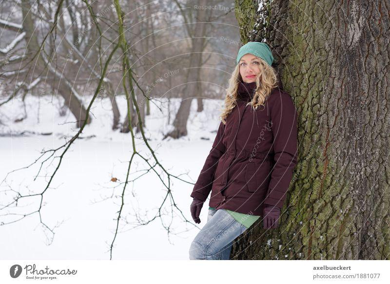 woman leaning against tree in winter landscape Lifestyle Winter Schnee Mensch feminin Frau Erwachsene 1 30-45 Jahre Natur Baum Park Wald Mode Jeanshose Jacke
