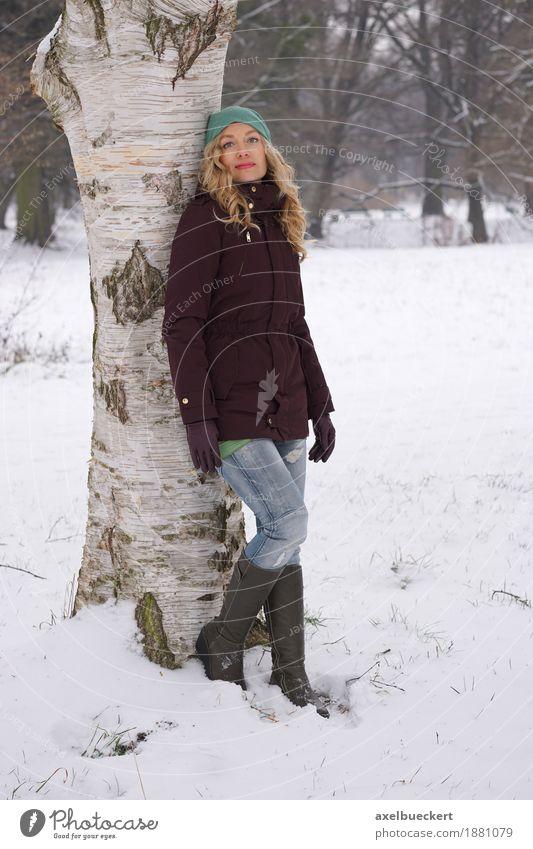 woman leaning against tree in winter Lifestyle Freizeit & Hobby Winter Schnee Mensch feminin Frau Erwachsene 1 30-45 Jahre Natur Baum Park Wald Mode Jeanshose