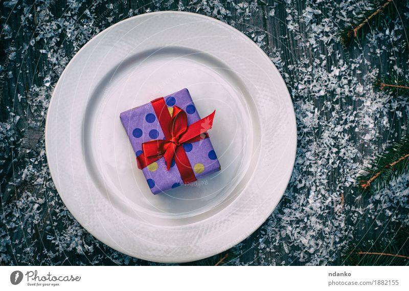 Verpacktes Geschenk mit einem roten Band auf einer weißen Platte alt Weihnachten & Advent Baum Speise Schnee Holz grau Feste & Feiern oben