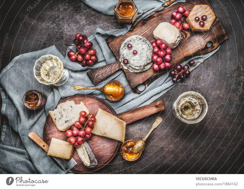 Verschiedene Käse auf Schneidebrettern mit Trauben und Wein Lebensmittel Milcherzeugnisse Frucht Dessert Ernährung Büffet Brunch Festessen Getränk Geschirr
