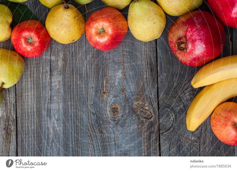 Bananen, Granatäpfel, Äpfel und Birnen auf einer grauen Holzoberfläche rot gelb Essen Herbst natürlich Garten Lebensmittel oben Frucht Ernährung frisch Aussicht